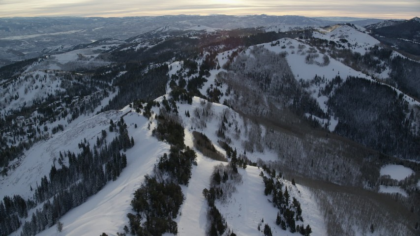 6K stock footage aerial video fly over snowy mountain ridge at sunrise in wintery Wasatch Range, Utah Aerial Stock Footage | AX124_104