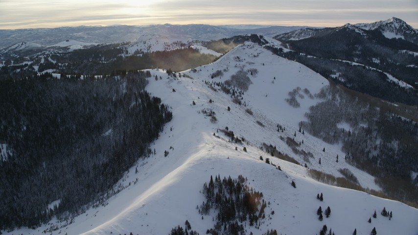 6K stock footage aerial video approach snowdrifts blowing off of mountains in the Wasatch Range, Utah at sunrise Aerial Stock Footage | AX124_108