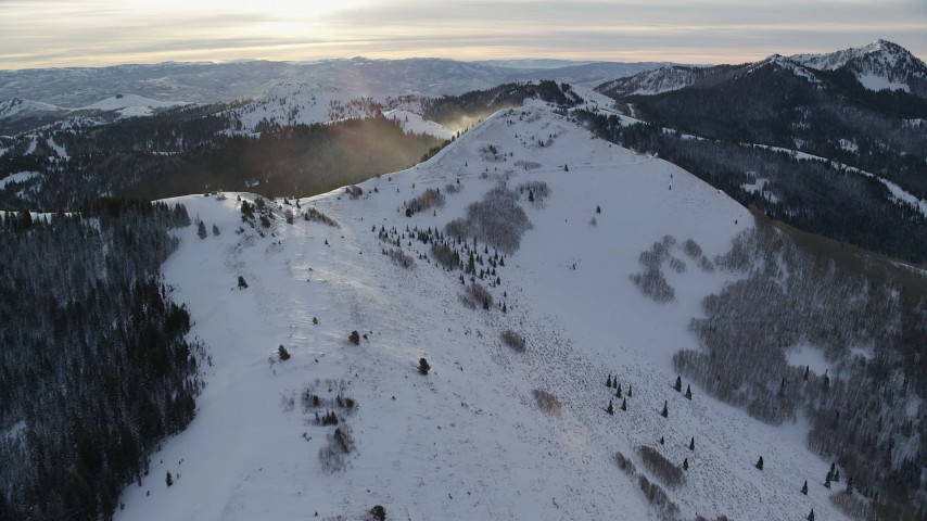 6K stock footage aerial video of snowdrifts on a wintery Wasatch Range mountain at sunrise in Utah Aerial Stock Footage | AX124_109