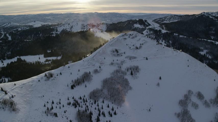 Snowdrift Plume on a Wintery Mountain Peak at Sunrise in Utah Aerial Stock Footage | AX124_110
