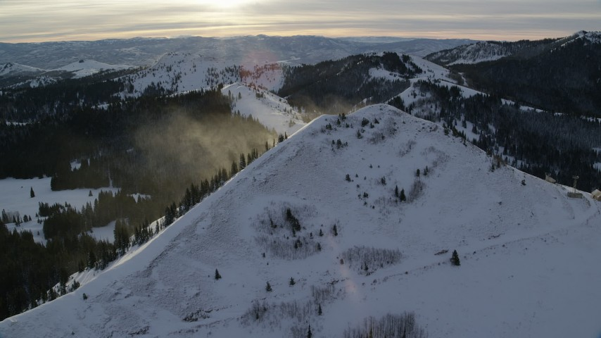 Approach Snowdrift off a Snowy Wasatch Range Peak at Sunrise in Utah Aerial Stock Footage   AX124_111