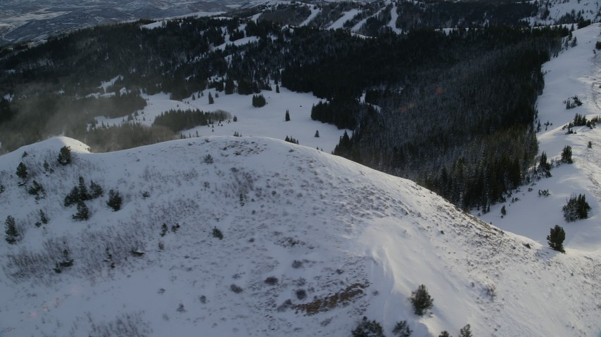 Orbit a Snowdrift on a Snowy Peak near Forest at Sunrise in Utah Aerial Stock Footage | AX124_113