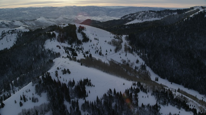 6K stock footage aerial video orbit over snow mountain in wintertime at sunrise in the Wasatch Range, Utah Aerial Stock Footage | AX124_115