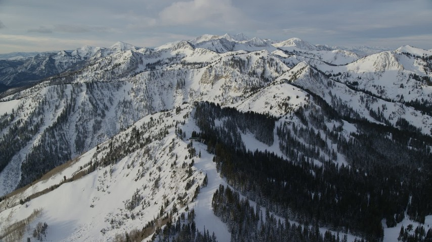 Pan Right across Snow Mountains in Wasatch Range at Sunrise Aerial Stock Footage | AX124_124