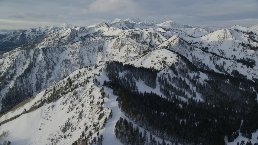 6K stock footage aerial video pan across snow mountains in Wasatch Range at sunrise in Utah Aerial Stock Footage | AX124_124