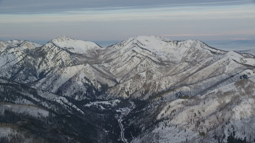 Wasatch Range Mountains in Wintertime with Snow at Sunrise Aerial Stock Footage | AX124_133