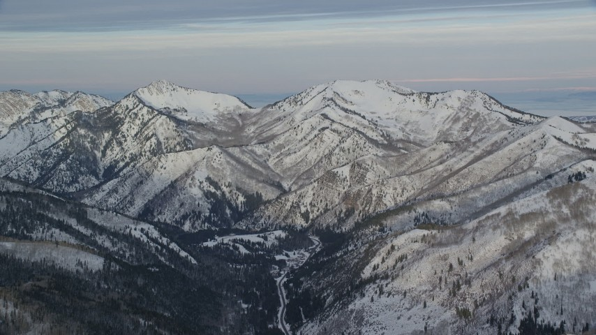 6K stock footage aerial video of Wasatch Range mountains in wintertime with snow at sunrise, Utah Aerial Stock Footage | AX124_133