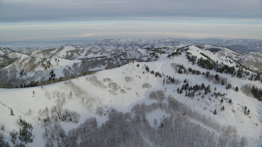 Approach the Top of a Snow Mountain at Sunrise in Utah's Wasatch Range Aerial Stock Footage | AX124_137