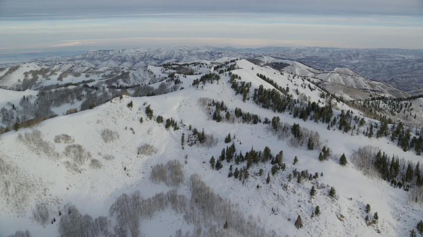 6K stock footage aerial video approach the top of a snow mountain at sunrise in Utah's Wasatch Range Aerial Stock Footage | AX124_137