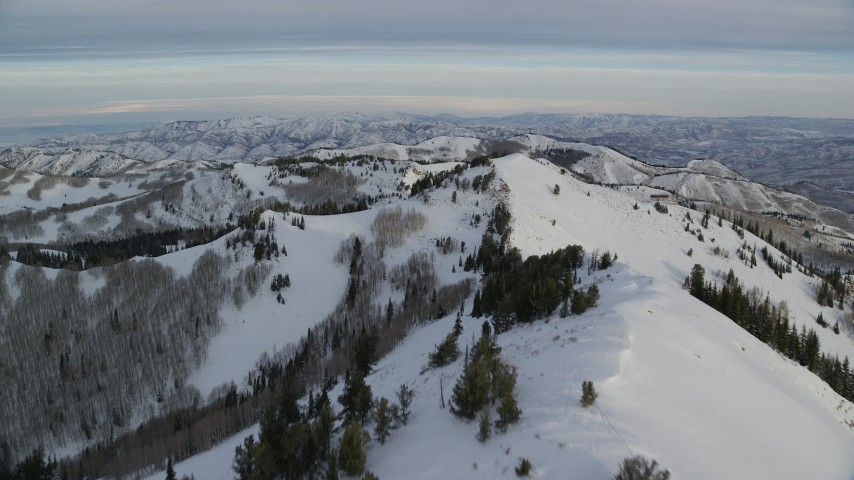 6K stock footage aerial video fly over a peak with snow toward a second peak at sunrise in Utah's Wasatch Range Aerial Stock Footage   AX124_138