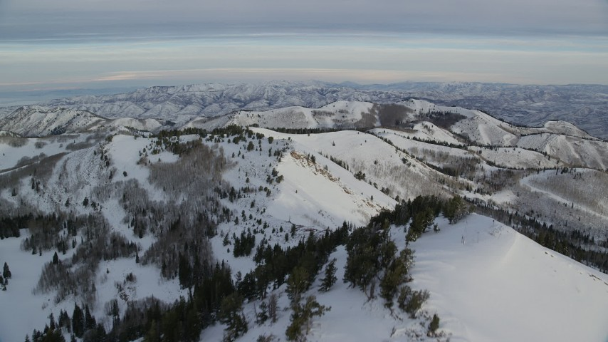 6K stock footage aerial video of flying over a snowy peak toward more wintery mountains at sunrise in Wasatch Range, Utah Aerial Stock Footage | AX124_139