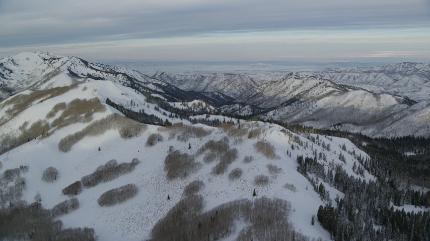 6K stock footage aerial video orbit over a snowy mountain ridge in Utah's Wasatch Range at sunrise Aerial Stock Footage | AX124_142