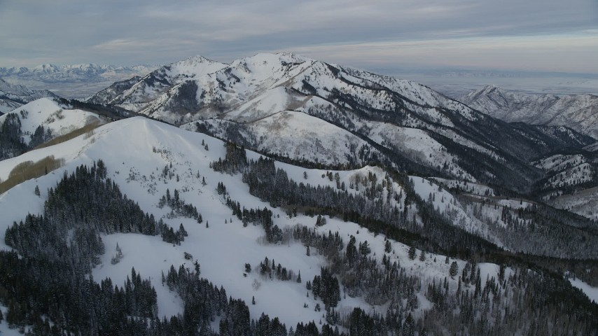 6K stock footage aerial video of snow mountains in Utah's Wasatch Range at sunrise Aerial Stock Footage | AX124_144