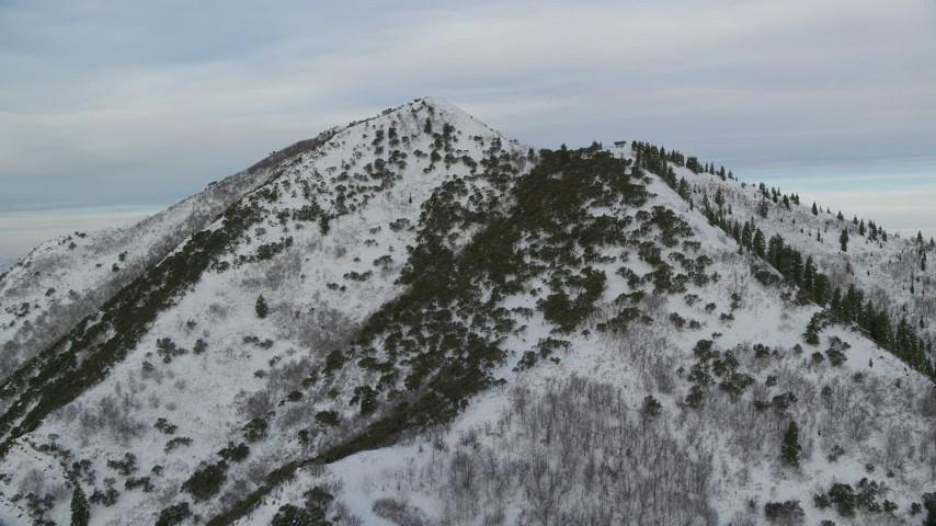6K stock footage aerial video of approaching top of Grandeur Peak with light snow at sunrise in Utah Aerial Stock Footage | AX124_172