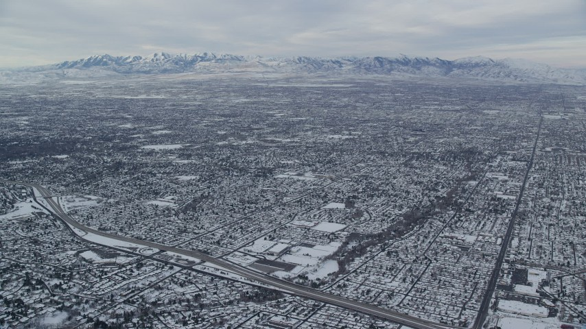 6K aerial video of Salt Lake City suburbs and Oquirrh Mountains in winter snow at sunrise, Utah Aerial Stock Footage | AX124_178