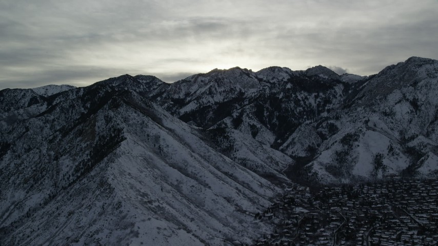 Wasatch Range Snow Mountains Bordering Suburbs at Sunrise in Utah Aerial Stock Footage   AX124_181