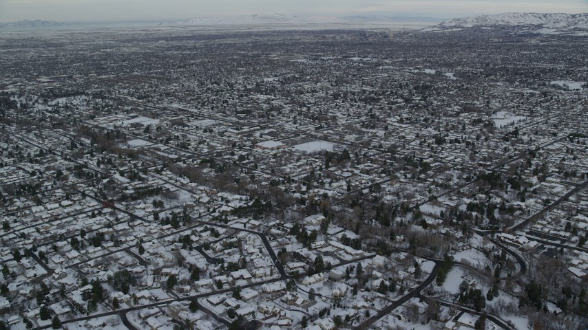 6K stock footage aerial video fly over snowy suburban rooftops in winter at sunrise in Salt Lake City, Utah Aerial Stock Footage | AX124_184