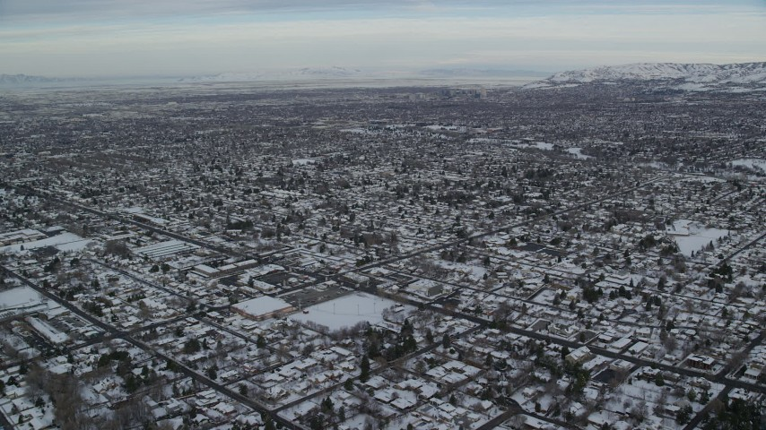 6K aerial video fly over suburban Salt Lake City neighborhoods with winter snow at sunrise, Utah Aerial Stock Footage | AX124_185