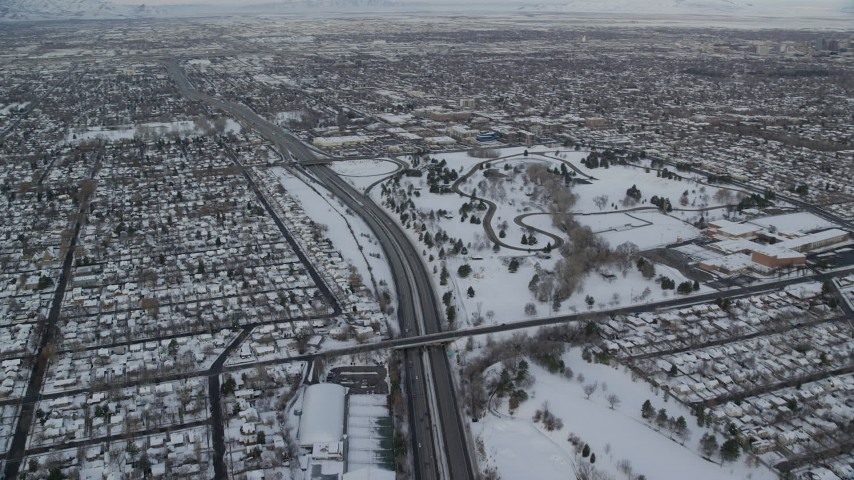 Orbit Interstate 80 through Snowy Salt Lake City and Tilt Up at Sunrise Aerial Stock Footage | AX124_188