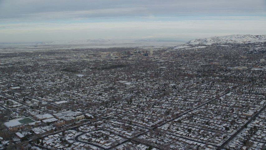 6K stock footage aerial video fly over suburban homes with snow toward Downtown Salt Lake City at sunrise in Utah Aerial Stock Footage | AX124_189