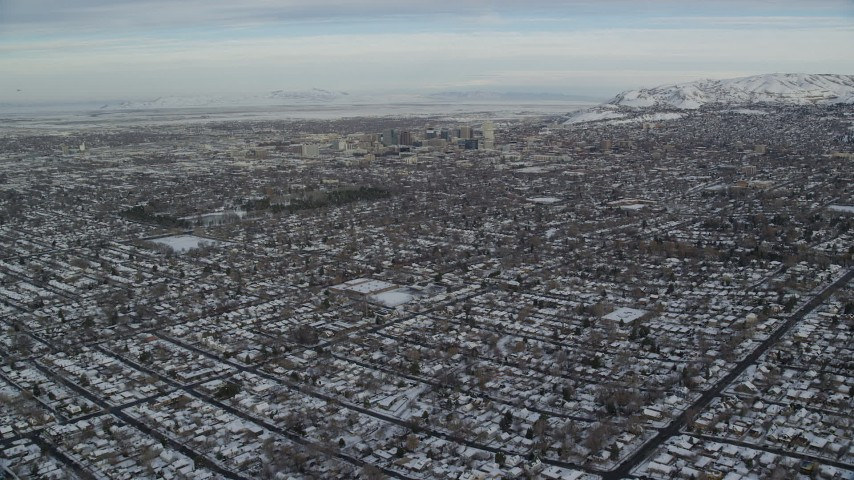 6K stock footage aerial video fly over suburbs with winter snow to approach Downtown Salt Lake City at sunrise in Utah Aerial Stock Footage | AX124_190