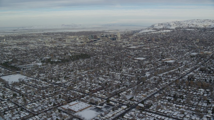 6K stock footage aerial video fly over snowy homes toward Downtown Salt Lake City at sunrise in Utah Aerial Stock Footage | AX124_191