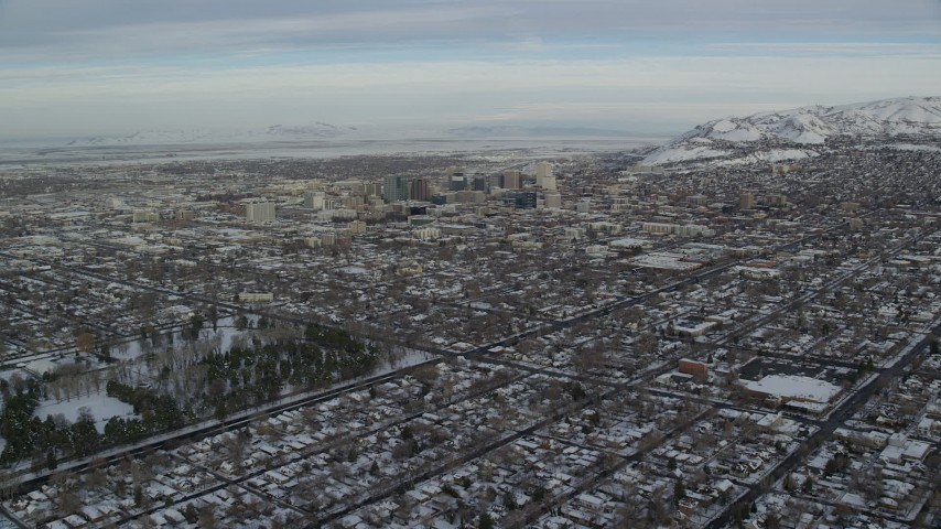 6K stock footage aerial video approach Downtown Salt Lake City from suburbs with snow at sunrise, Utah Aerial Stock Footage | AX124_192