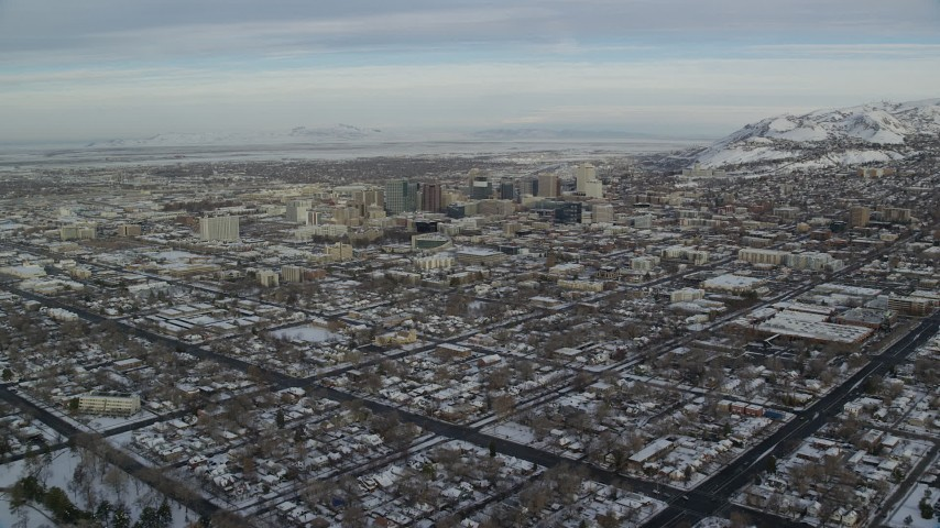 6K stock footage aerial video approach Downtown Salt Lake City with winter snow at sunrise in Utah Aerial Stock Footage | AX124_193