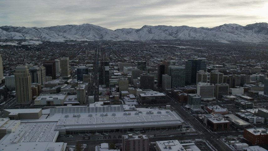 6K stock footage aerial video circle Downtown Salt Lake City and Salt Palace with winter snow at sunrise in Utah Aerial Stock Footage | AX124_207