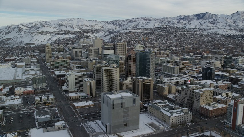 6K stock footage aerial video of circling Downtown Salt Lake City buildings with winter snow at sunrise, Utah Aerial Stock Footage | AX124_210
