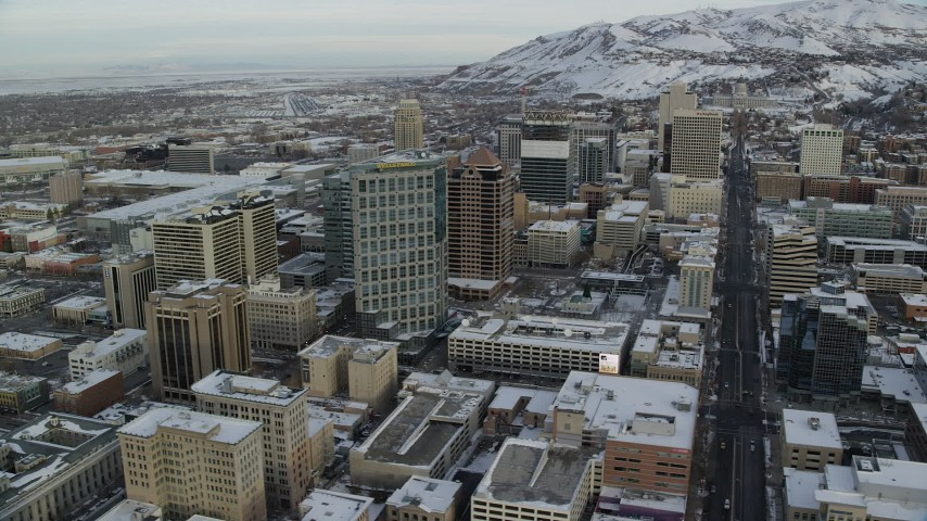 6K stock footage aerial video of circling Downtown Salt Lake City streets and buildings with winter snow at sunrise, Utah Aerial Stock Footage | AX124_211