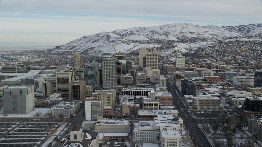 6K stock footage aerial video approach buildings in Downtown Salt Lake City with snow at sunrise in Utah Aerial Stock Footage | AX124_213