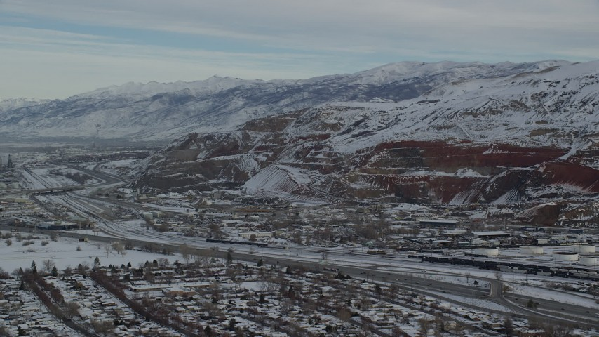 6K stock footage aerial video orbit Interstate 15 and train tracks by snowy mountains at sunrise in Salt Lake City, Utah Aerial Stock Footage | AX124_231