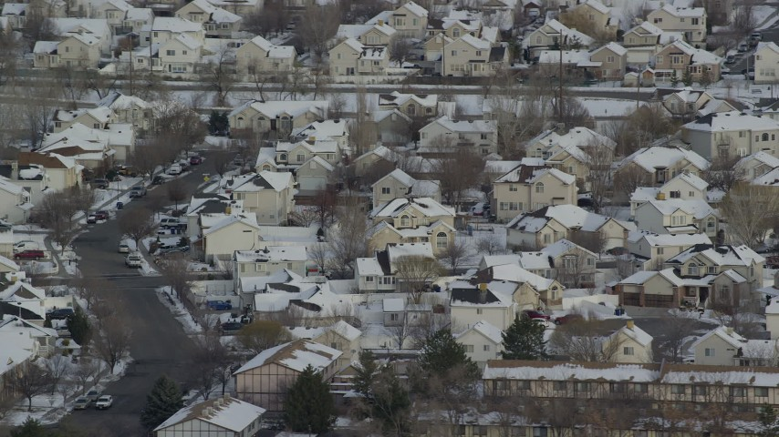 6K stock footage aerial video orbit Salt Lake City tract homes with snowy rooftops at sunrise, Utah Aerial Stock Footage | AX124_233