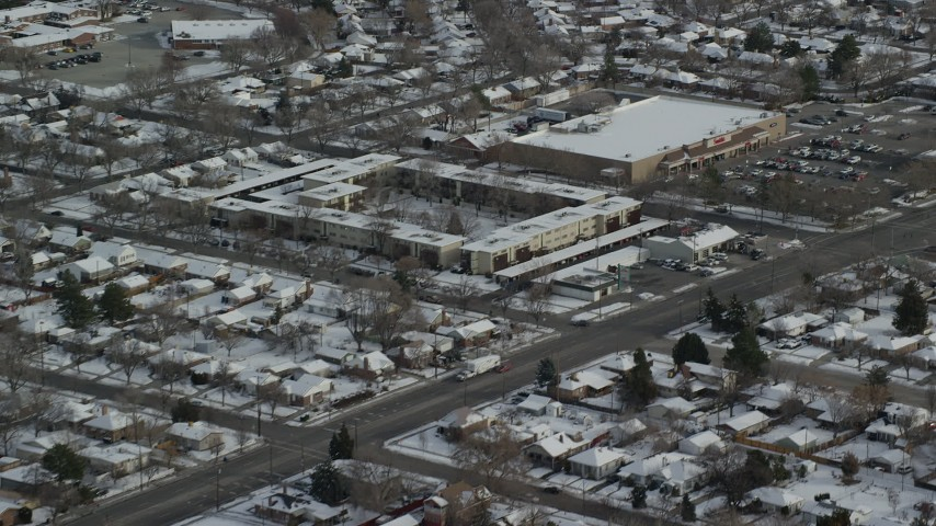 6K stock footage aerial video of suburban Salt Lake City neighborhoods and shopping center with winter snow in Utah Aerial Stock Footage | AX125_004