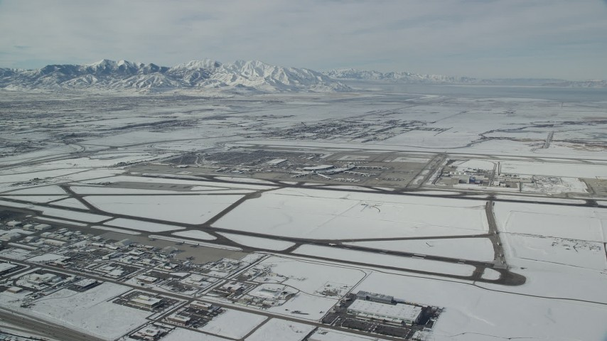 6K stock footage aerial video of Salt Lake City International Airport and jet on runway with winter snow in Utah Aerial Stock Footage | AX125_010