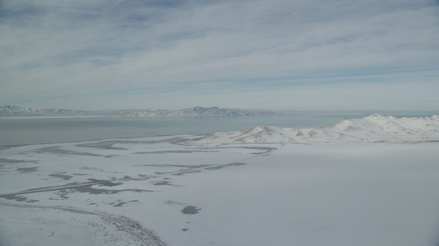 6K stock footage aerial video of Great Salt Lake and Antelope Island with snow mountains in winter in Utah Aerial Stock Footage | AX125_026