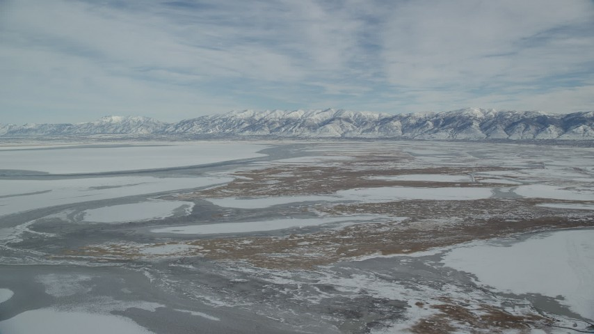 Orbit Snowy Wasatch Range Mountains and Frozen Marshlands in Winter Aerial Stock Footage | AX125_027