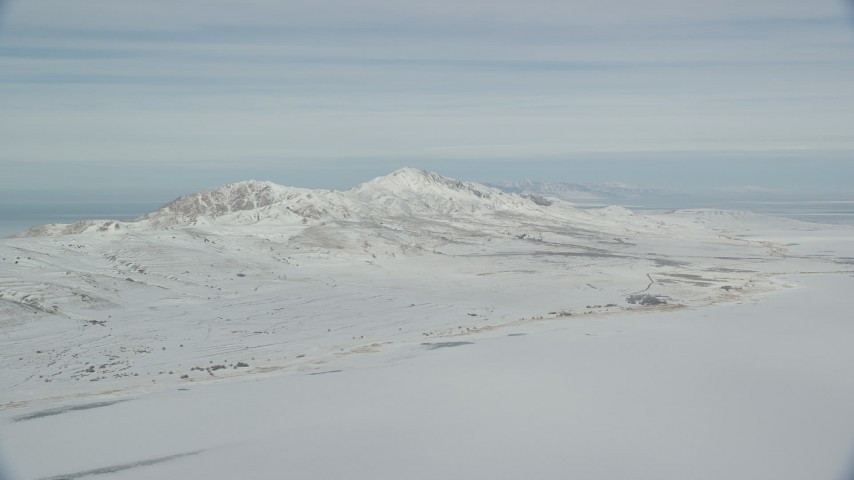 6K stock footage aerial video pan across snow mountains on Antelope Island in wintery Utah Aerial Stock Footage | AX125_029