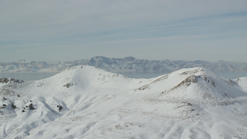 6K aerial video of frozen mountains on Antelope Island in wintertime in Utah Aerial Stock Footage   AX125_036