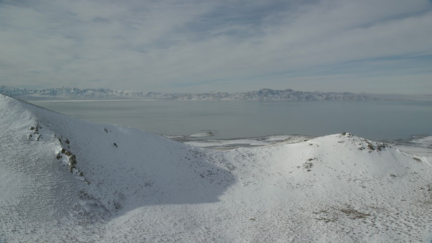 6K stock footage aerial video of Great Salt Lake seen from Antelope Island mountains in winter, Utah Aerial Stock Footage | AX125_037