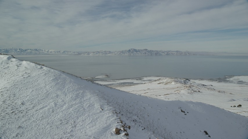 The Great Salt Lake seen from Snowy Mountain Summit on Antelope Island Aerial Stock Footage | AX125_038