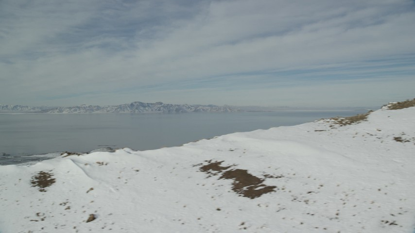 6K stock footage aerial video flyby snowy mountain ridge to reveal Great Salt Lake in Utah Aerial Stock Footage | AX125_039