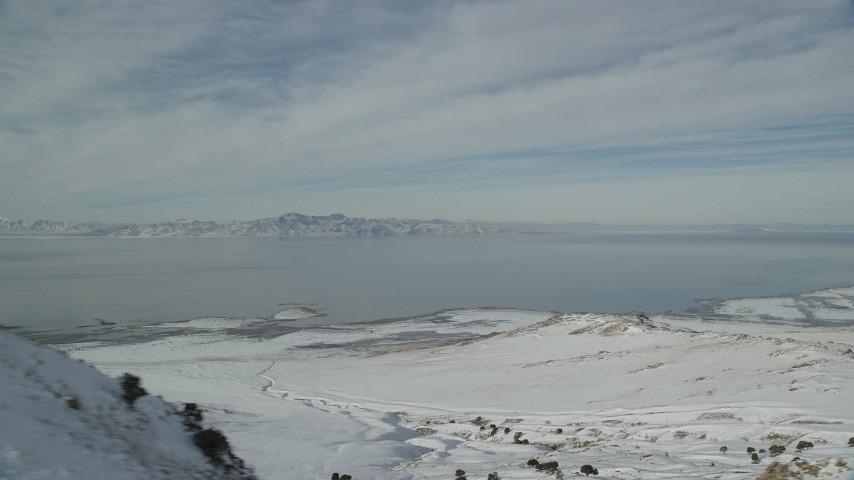 6K stock footage aerial video of Great Salt Lake seen from snowy ridge on Antelope Island in winter, Utah Aerial Stock Footage | AX125_040