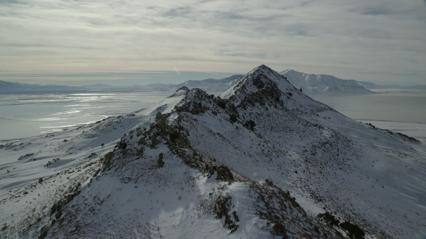 6K stock footage aerial video fly over snowy mountain ridge on Antelope Island in winter, Utah Aerial Stock Footage AX125_048 | Axiom Images