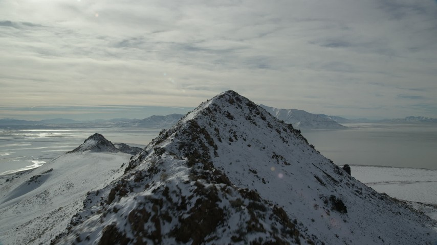 6K stock footage aerial video fly over and approach rocky peaks on Antelope Island in winter, Utah Aerial Stock Footage | AX125_050