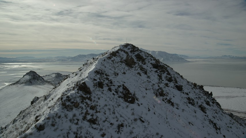 6K stock footage aerial video fly over snowy Antelope Island peak toward Great Salt Lake in winter, Utah Aerial Stock Footage | AX125_051