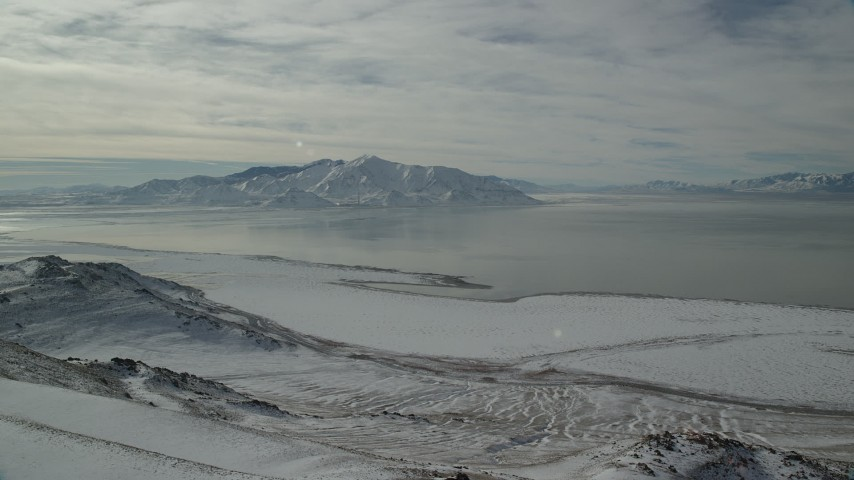 Approach Frozen Shore of Antelope Island and Great Salt Lake in Winter Aerial Stock Footage | AX125_052