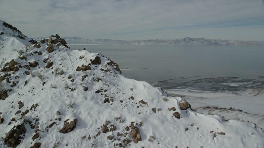 6K stock footage aerial video orbit a rocky slope to reveal bighorn sheep in winter snow, Antelope Island, Utah Aerial Stock Footage | AX125_066