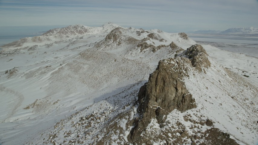 6K stock footage aerial video of flying over a jagged mountain ridge with winter snow on Antelope Island, Utah Aerial Stock Footage | AX125_077